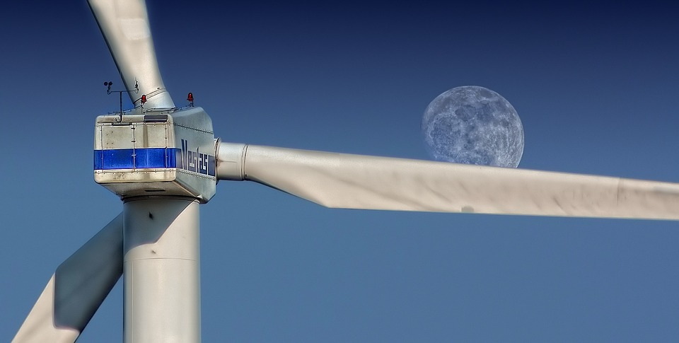 Photo d'une éolienne en gros plan avec en fond de plan la lune