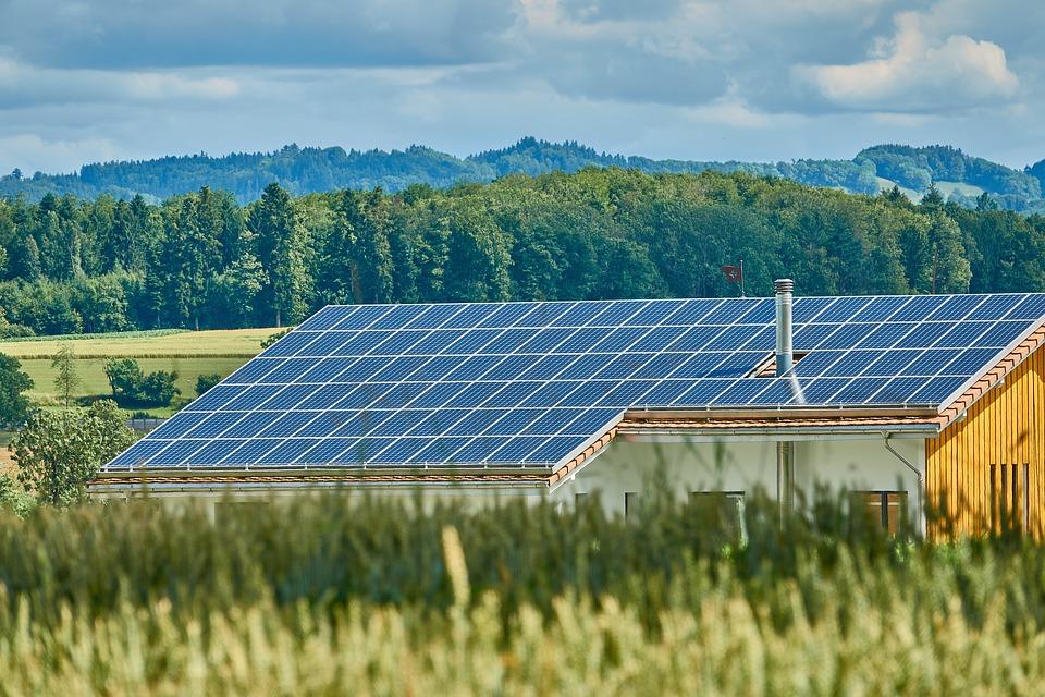 Photo de panneaux solaires (forme d'énergie solaire) sur le toit d'une maison dans un champ