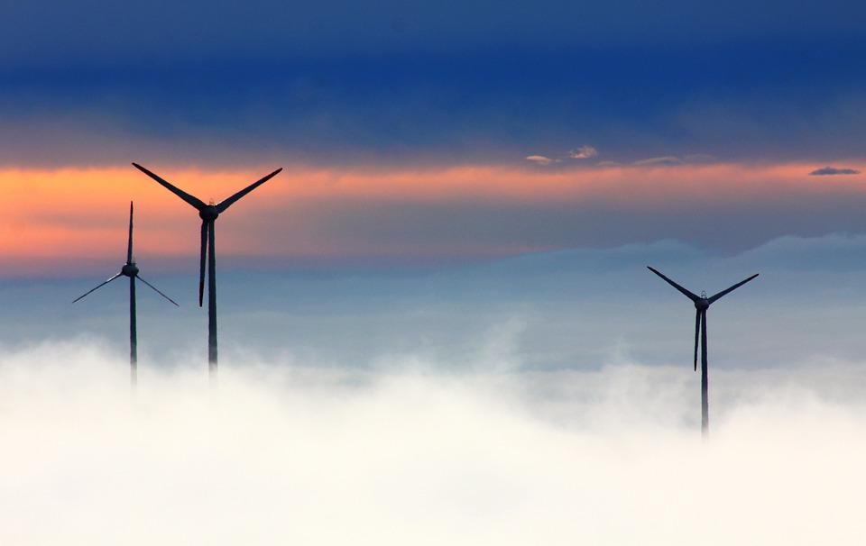 Photo de plusieurs éoliennes avec des nuages (exemple d'alternatives durables)